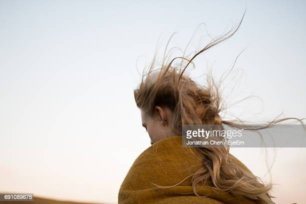 low angle view of young woman with tousled hair against clear sky - windswept stock pictures, royalty-free photos & images