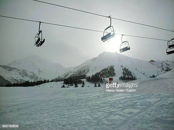 Low Angle View Overhead Cable Cars Above Snow Covered Field