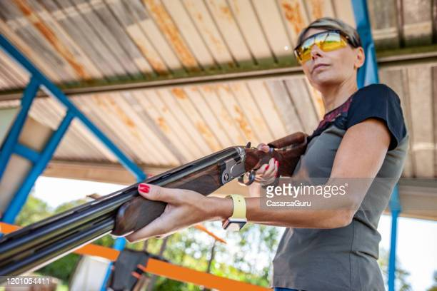 low angle view portrait of determined adult woman holding loaded shotgun at shooting range - stock photo - clay pigeon shooting stock pictures, royalty-free photos & images