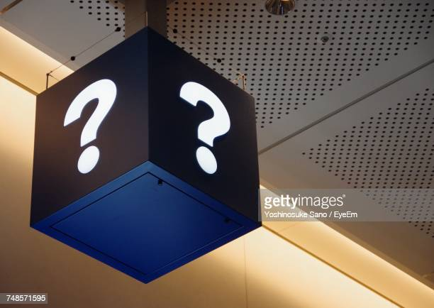 low angle view question mark sign on box hanging from ceiling - segnale informativo foto e immagini stock