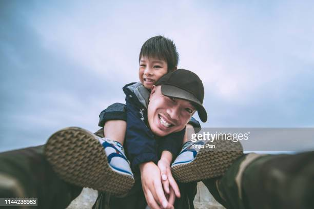 low angle view selfie portrait of the son sitting on his father's shoulder, shanghai, china - wide angle stock pictures, royalty-free photos & images