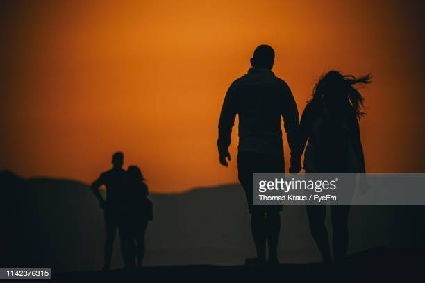 low angle view silhouette of couple holding hands standing against sky during sunset - four people stock pictures, royalty-free photos & images