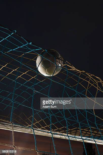 low angle view soccer ball in goal at night - scoring a goal stock pictures, royalty-free photos & images