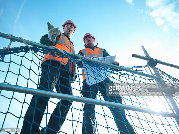 Low angle view through scaffolding of builders holding plans on factory roof