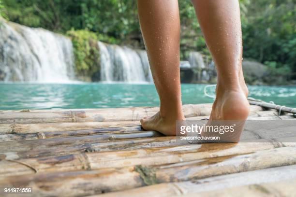 mulher de vista de ângulo baixo andando na jangada de bambu no sentido cachoeira incrível no conceito de clima tropical de natureza - azul turquesa - fotografias e filmes do acervo