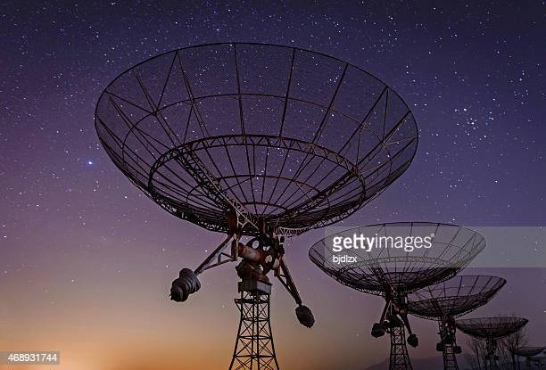 Low angled view of radio telescopes with Milky Way in sky