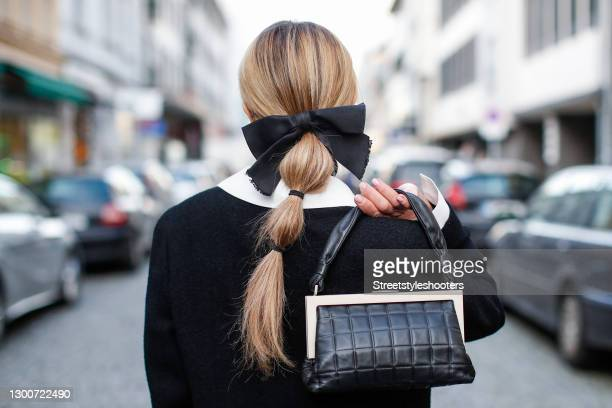 Low bubble ponytail hairstyle, a black bow hair clip by Chanel and a black and white bag by Chanel as a detail of influencer Gitta Banko during a...