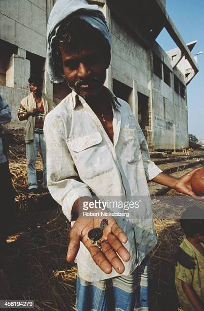 A low caste man with a handful of coins in Bihar India circa 1995