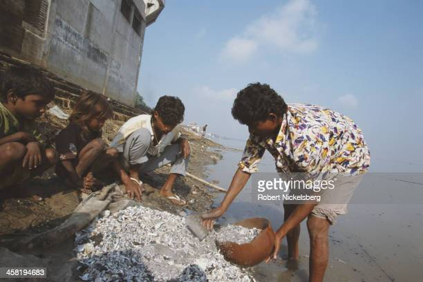 Low caste people sweep up the ashes after a cremation on the banks of the River Ganges India circa 1995 They are from the Domar caste of the Dalit or...