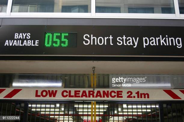 low clearance of 2.1 metres and parking bay count signs at the entrance to a short-stay parking garage - meter unit of length stock pictures, royalty-free photos & images