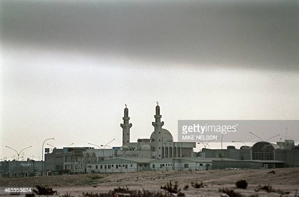 Low cloud of smoke hangs over a mosque 13 March 1991 in Kuwait City as oil wells set alight by Iraqi occupation forces continue to burn two weeks...