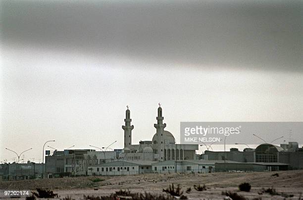 A low cloud of smoke hangs over a mosque 13 March 1991 in Kuwait City as oil wells set alight by Iraqi occupation forces continue to burn two weeks...