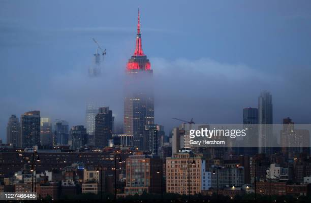 Low clouds float through midtown Manhattan past the Empire State Building as the sun sets in New York City on May 27 2020 as seen from Jersey City NJ