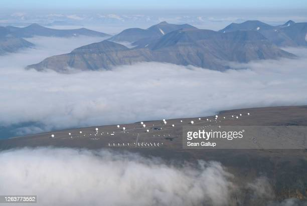 Low clouds hang near the Svalbard Satellite Station on Svalbard archipelago in a view through a passenger plane window on August 02 2020 near...