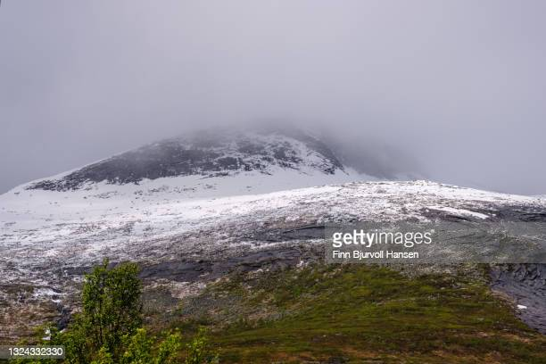 low clouds over a snowcapped mountain in northern norway - finn bjurvoll photos et images de collection