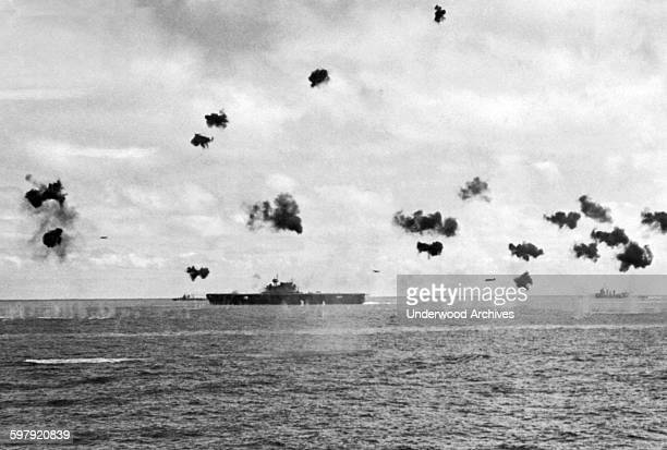Low flying Japanese torpedo planes come in from the right flying amidst bursting antiaircraft shells as they aim for a US Navy aircraft carrier in...