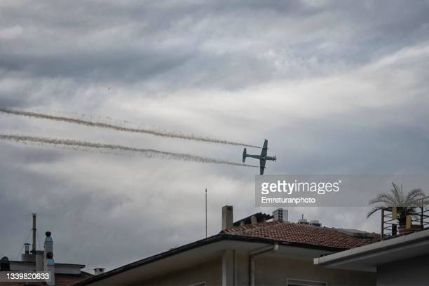 low flying turbo prop plane over the rooftops - emreturanphoto stock pictures, royalty-free photos & images