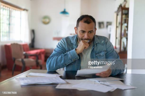 de mens die van het lage inkomen zijn huisfinanciën controleert en ongerust kijkt - colombia land stockfoto's en -beelden
