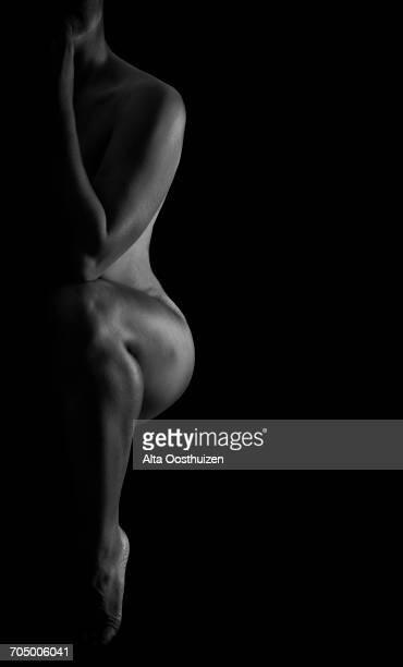 low key black and white photo of a woman posing - silueta mujer desnuda fotografías e imágenes de stock