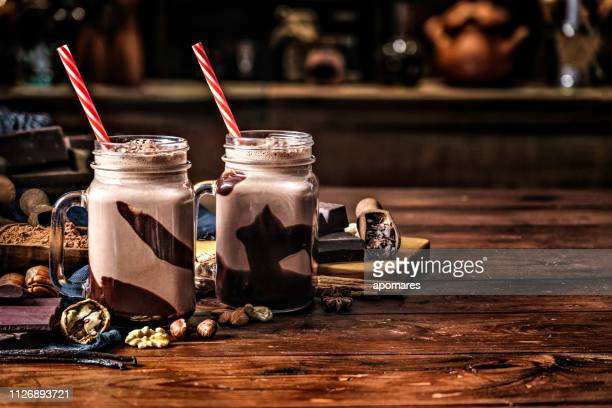 low key chocolate smoothies on a table in a rustic kitchen - milkshake imagens e fotografias de stock