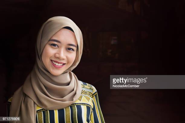 low key female muslim young adult smiling portrait dark background - muslim woman darkness stock photos and pictures