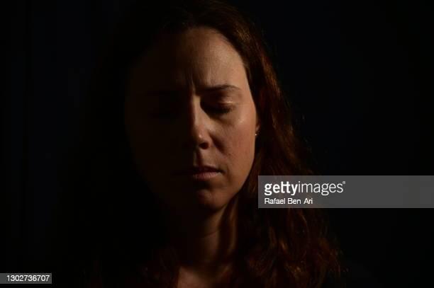 low key frontal portrait of upset adult woman face with eye closed - rafael ben ari stock-fotos und bilder