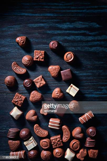low key image of a variety of chocolate and bombones on a blue rustic table with copy space - navy blue stock pictures, royalty-free photos & images