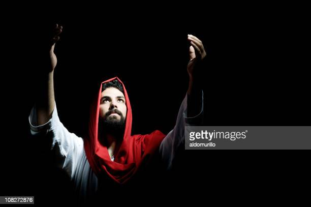 low key lit jesus christ lifting arms toward sky - jesus is alive stock pictures, royalty-free photos & images
