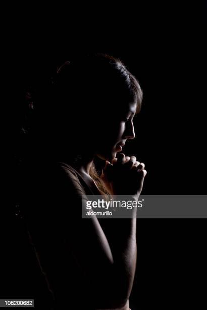 Low Key Lit Portrait of Young Woman Praying