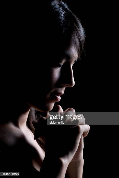 Low Key Lit Side View of Young Woman Praying