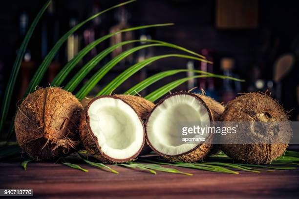 low key of coconuts on wooden rustic table - coconut stock pictures, royalty-free photos & images