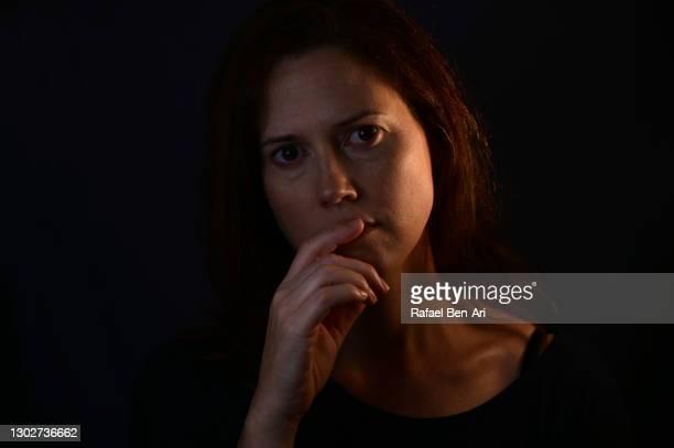 low key portrait of a worried adult woman face covering her mouth looking at camera - rafael ben ari bildbanksfoton och bilder
