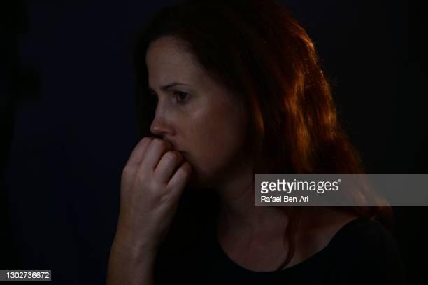 low key portrait of a worried adult woman face looking away from camera - rafael ben ari bildbanksfoton och bilder