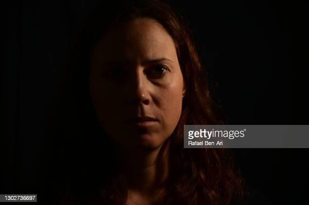 low key portrait of an adult woman face looking at camera - rafael ben ari photos et images de collection