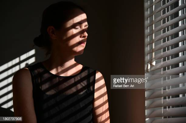 low key portrait of an adult woman face with eyes closed hit by a sunlight entering through window - rafael ben ari stockfoto's en -beelden