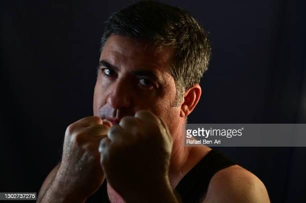 low key portrait of an aggressive martial arts boxer mature adult man face looking at camera - rafael ben ari stock-fotos und bilder