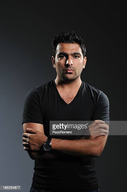 low key portrait of pakistani man with arms crossed - handsome pakistani men stock photos and pictures