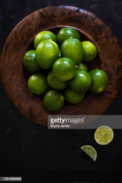 low key shot of limes in a wooden bowl - brycia james stock pictures, royalty-free photos & images
