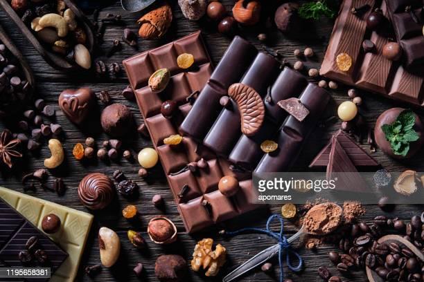 low-key variatie van chocolade en bombones met cacaopoeder en gedroogde vruchten in ouderwetse stijl - bordeauxrood stockfoto's en -beelden