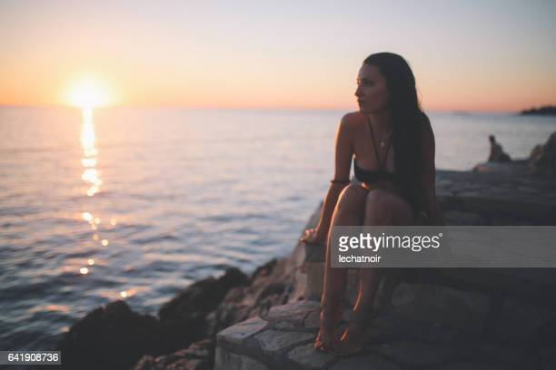 Lage belangrijke vintage beeld van een vrouw op de rotsachtige strand