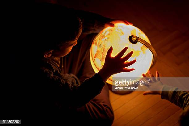 Low light portrait of boy with illuminated globe