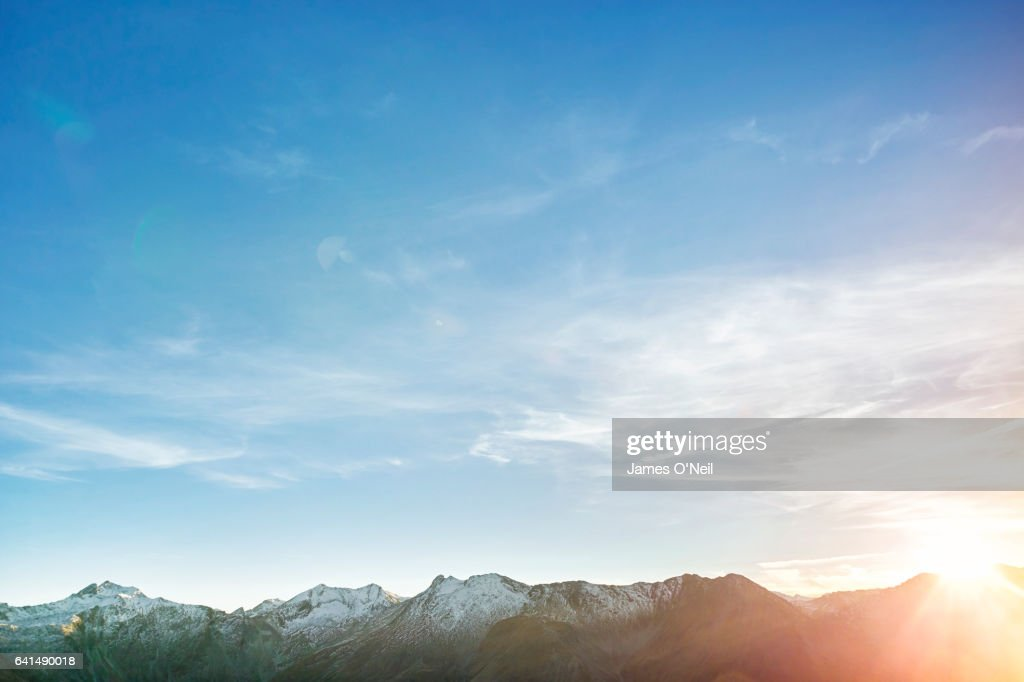 Low mountain range with expanse of sky and sun flare : Stock Photo
