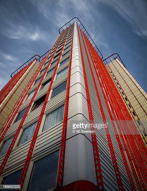 CONTENT] A low perspective angle on a West London tower block/ council estate on a sunny blue sky day The red and white building is located on...