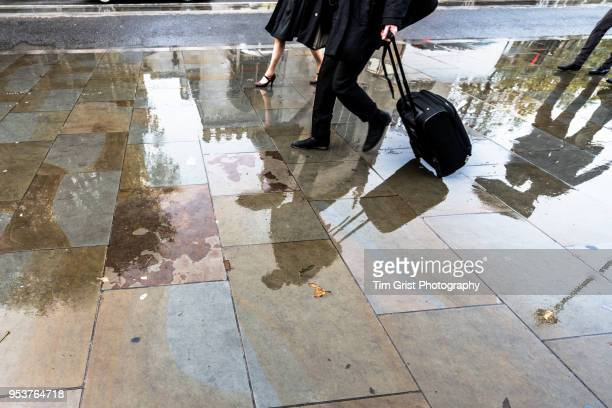low section and reflection of people with wheeled travel case - mens dress shoes stock pictures, royalty-free photos & images