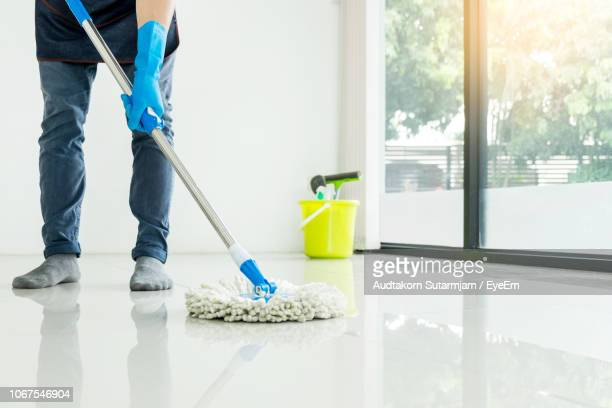 low section man cleaning floor with mop at home - sweeping stock pictures, royalty-free photos & images