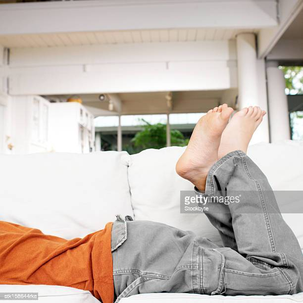 low section of a boys legs lying on a sofa - teen boy barefoot stock photos and pictures