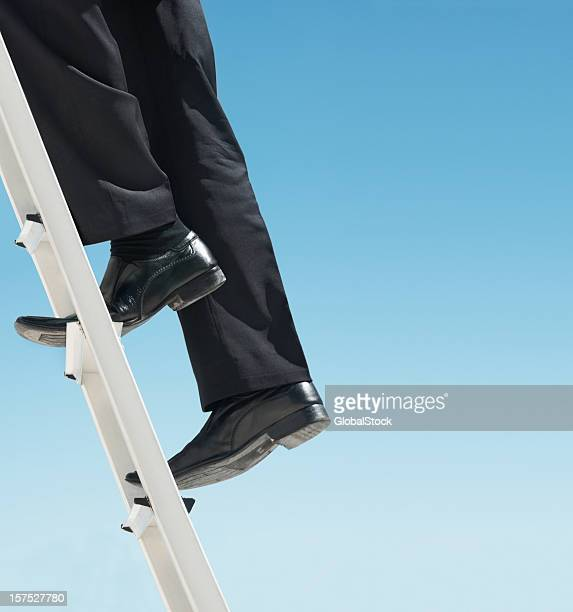 Low section of a business man climbing the ladder
