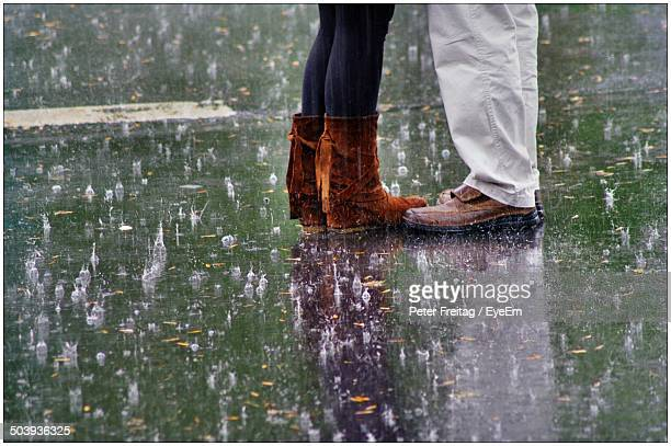 low section of a couple standing in rain - romantic rainy day stock photos and pictures