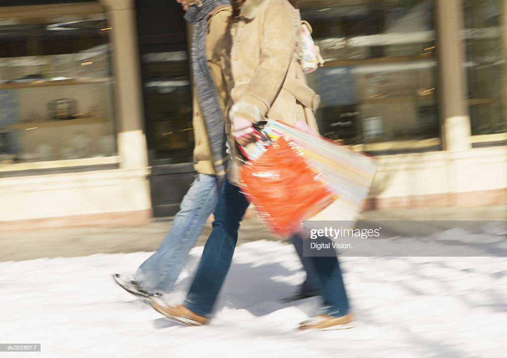 Low Section of a Couple Walking on a Snow-Covered Pavement, Carrying Shopping Bags : Stock Photo