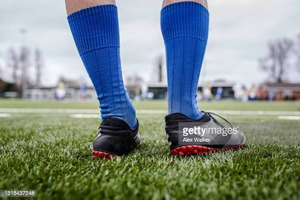 low section of a football player with long blue socks and black training shoes standing on grass - club football stock pictures, royalty-free photos & images